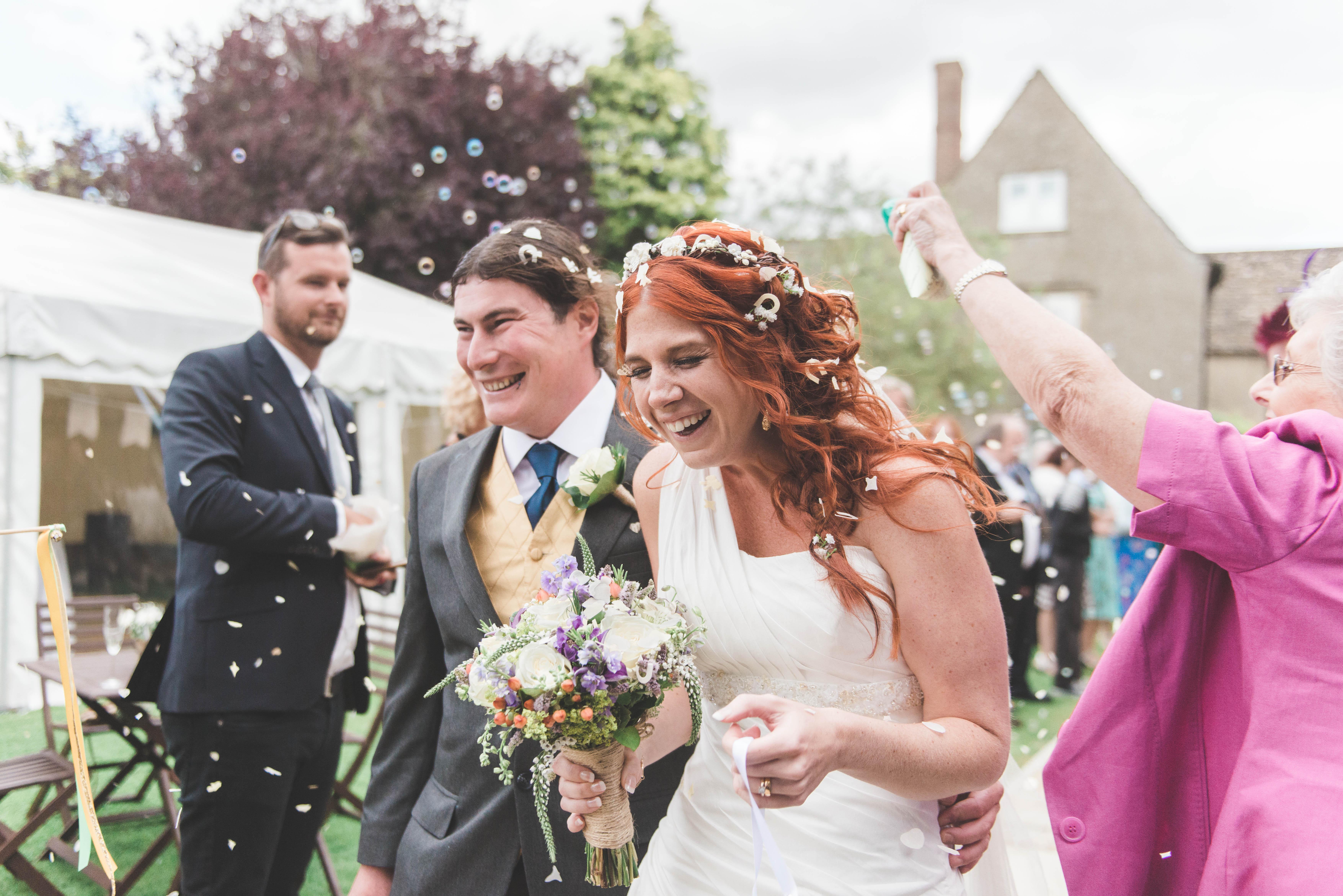 Stockholm trouwfotograaf - Bruid en bruidegom worden bedolven onder confetti tijdens hun bruiloft in Engeland