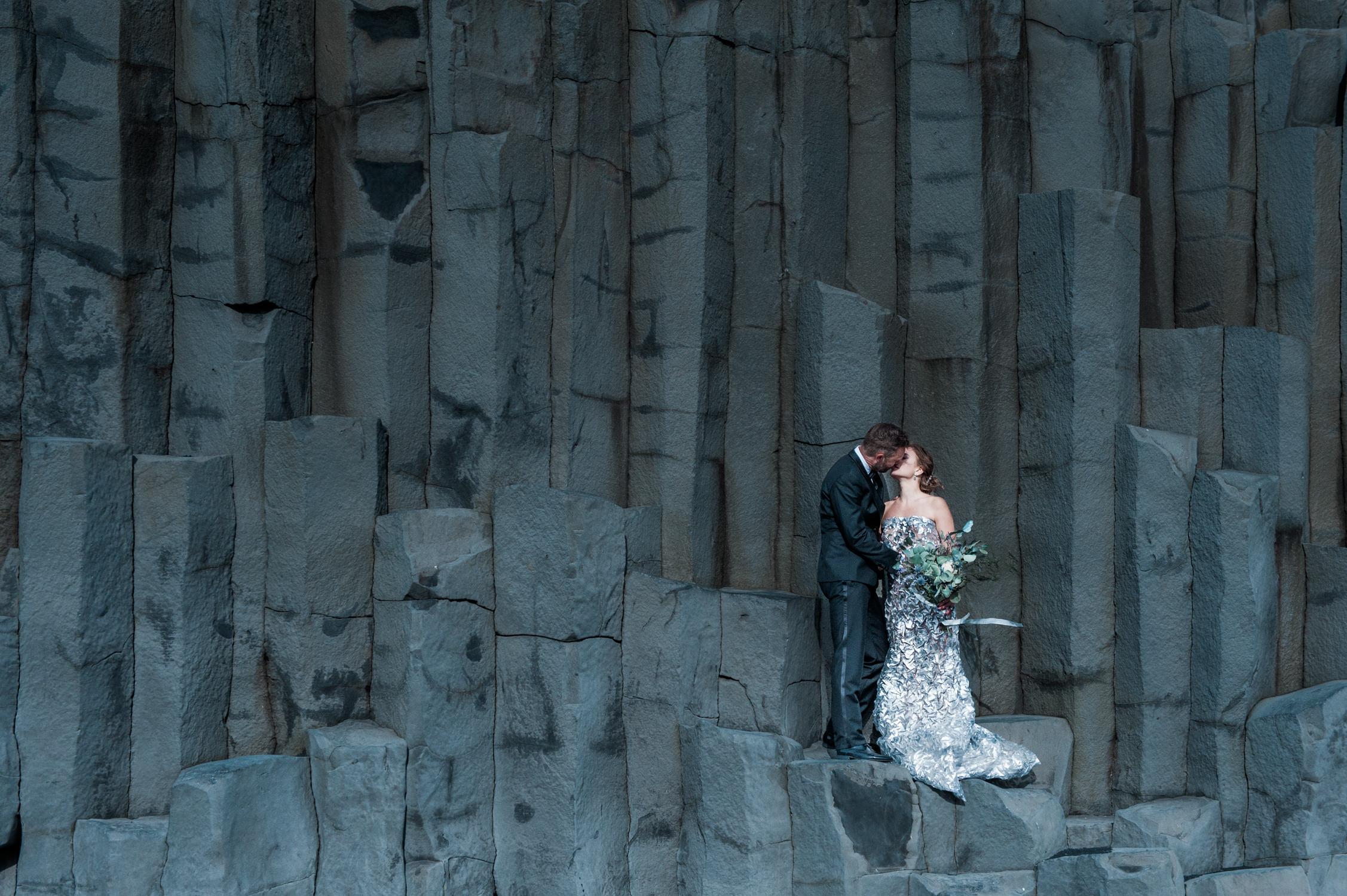 Een bruid en bruidegom op het zwarte strand (of black sand beach) in Vik op IJsland