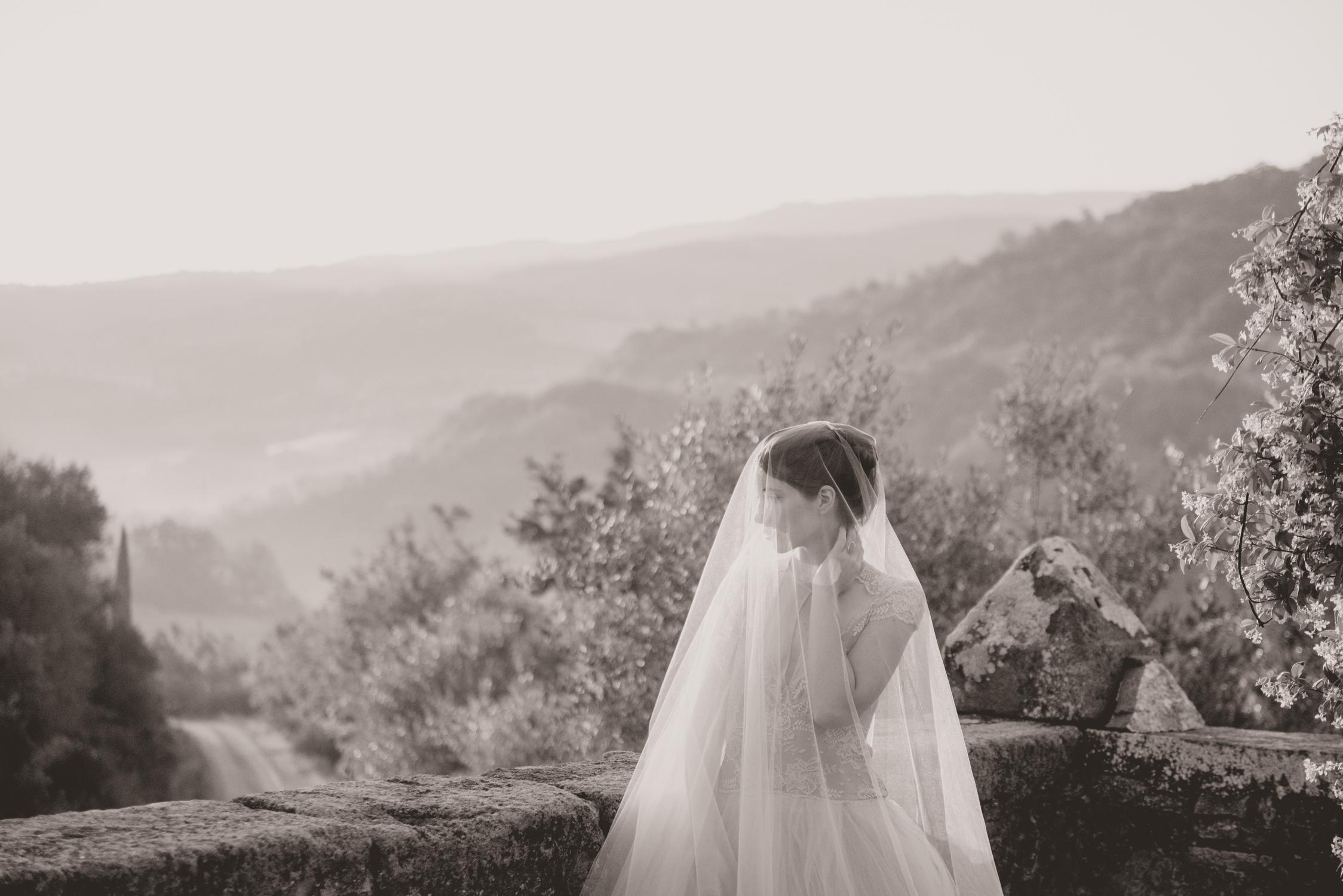 Een bruid geniet van een Toscaans uitzicht in zwart-wit