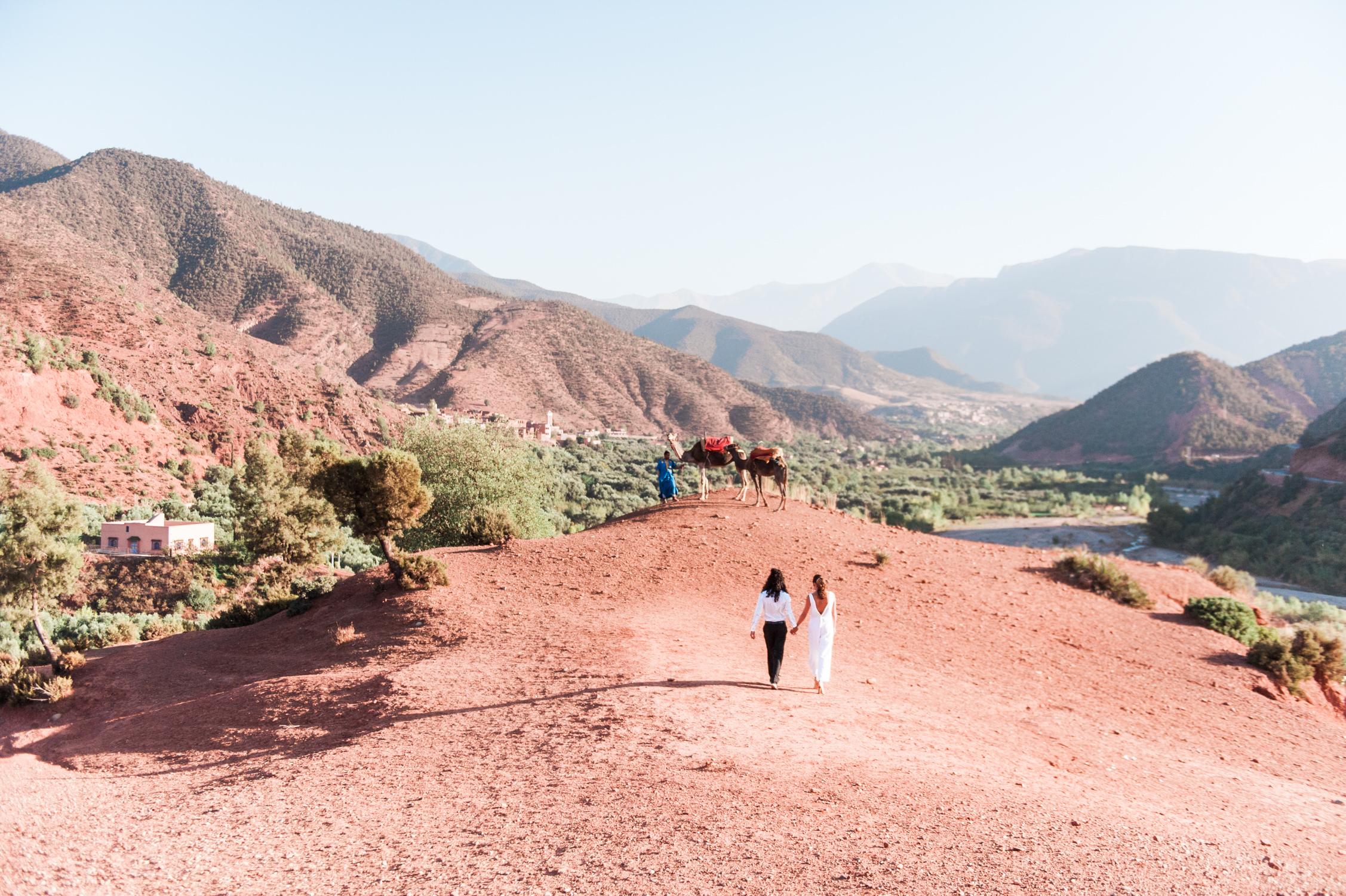 Een in een jumpsuit en een bruidegom met lang haar wandelen in de bergen, vastgelegd door een trouwfotograaf in Griekenland