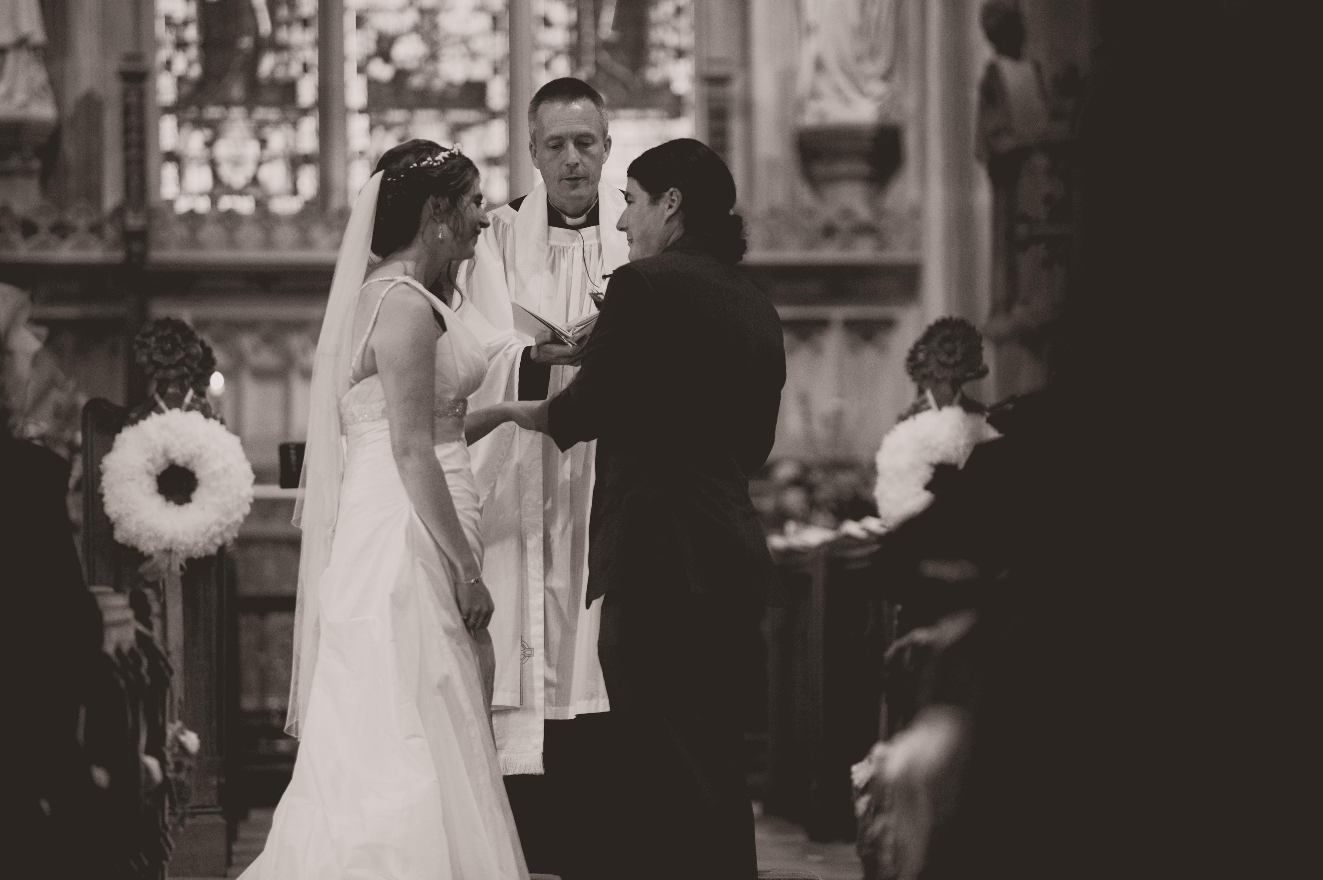 Bruidspaar staan bij het altaar tijdens hun bruiloft in Engeland