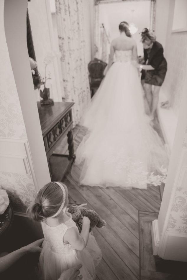 Bruidsmeisje kijkt naar bruid in trouwjurk, gefotografeerd door Wit Photography