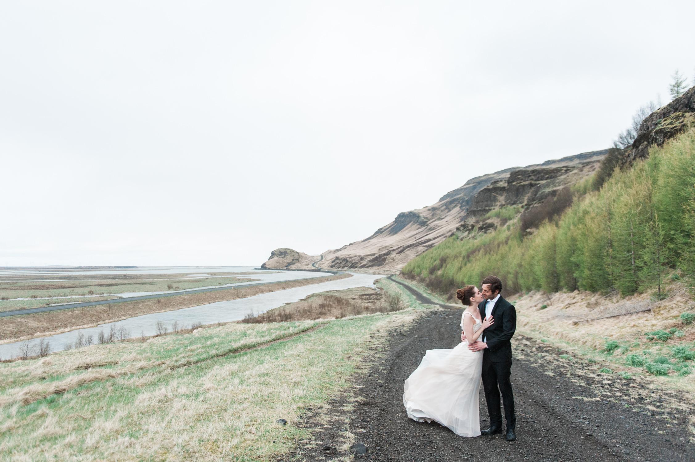 Een bruid en bruidegom op een verlaten weg in IJsland