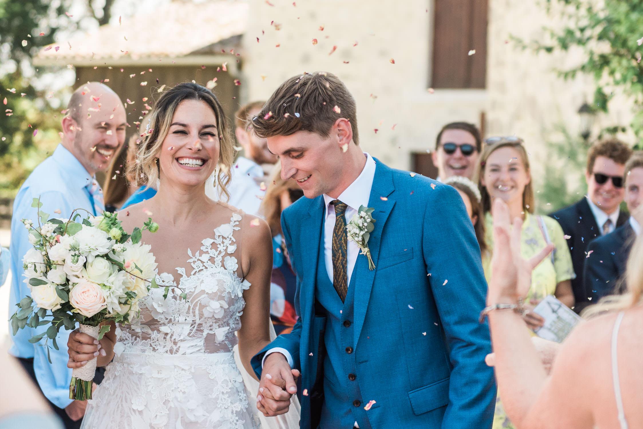 Een bruidspaar wordt bedolven onder confetti op hun bruiloft op een Frans kasteel in de Lot et Garonne regio