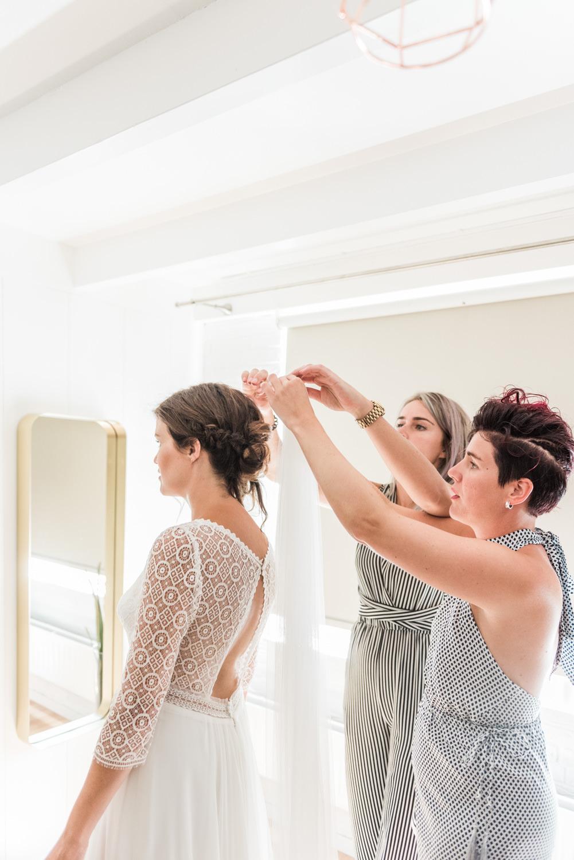 Een bruidsmeisje en een Maid of Honour helpen de bruid met aankleden en haar sluier in doen.