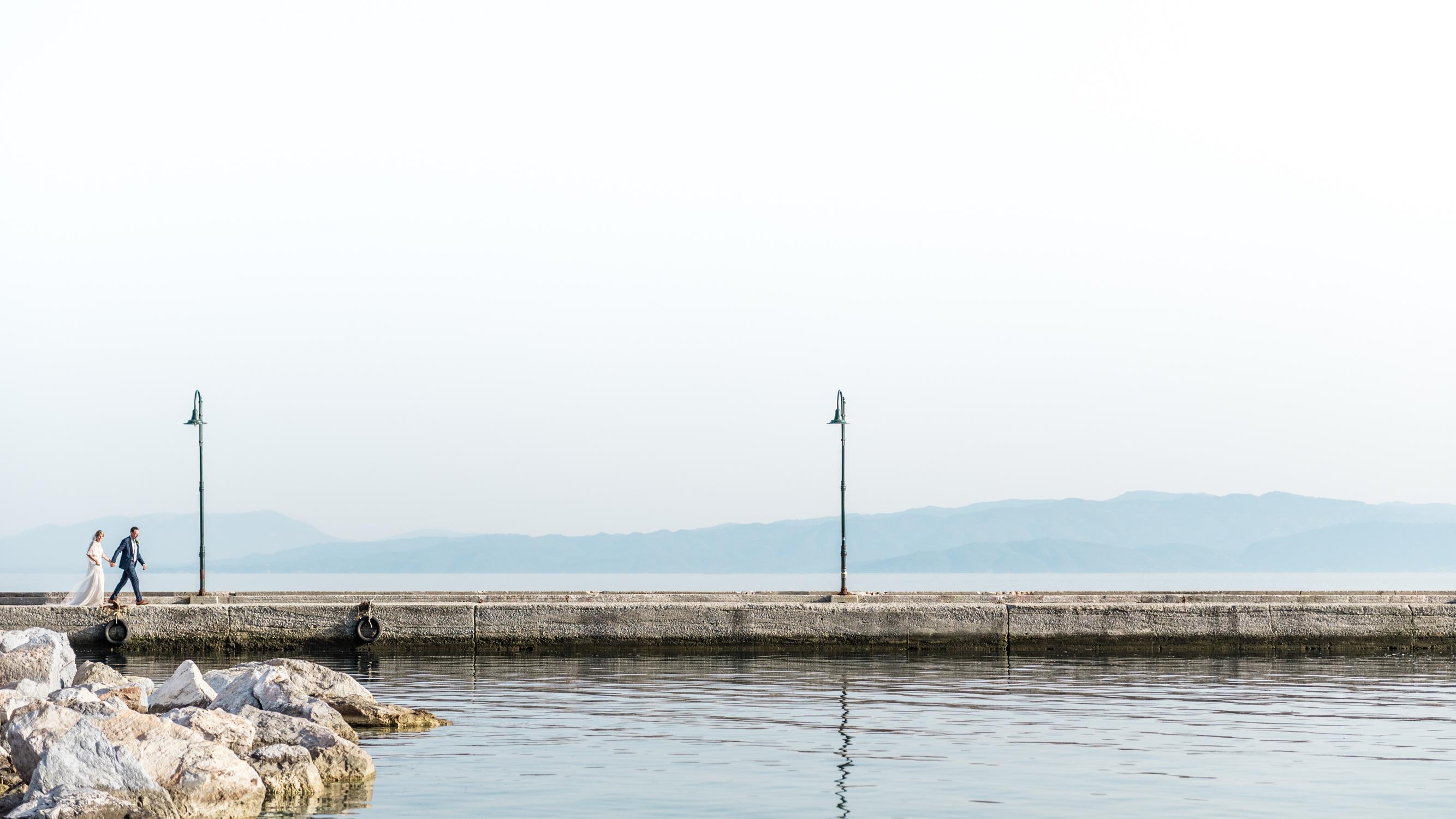 Een bruid en bruidegom op een kade in een haven in Griekenland