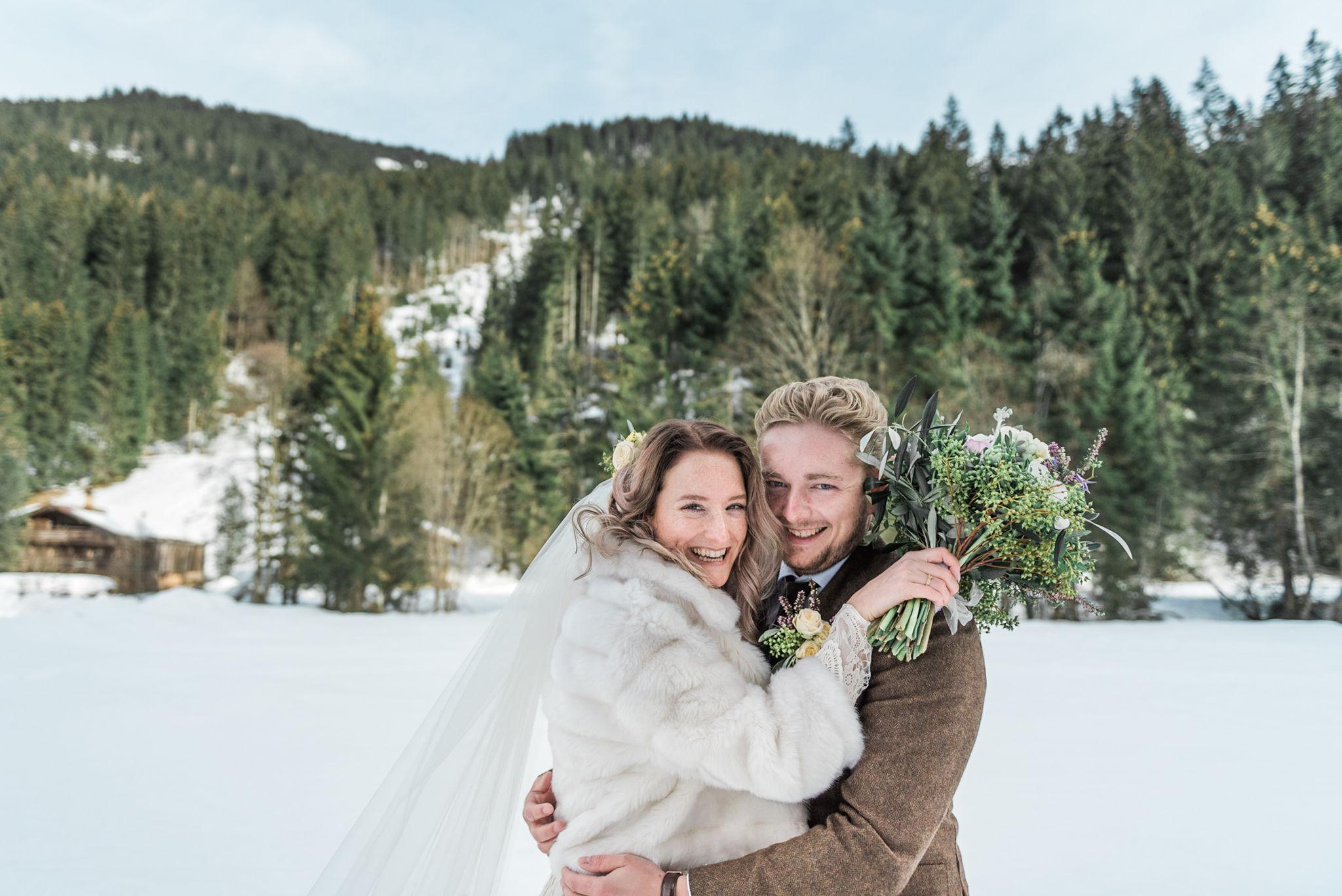 Bruidspaar met een bruidsboeket voor besneeuwde bergen tijdens hun bruiloft in Oostenrijk
