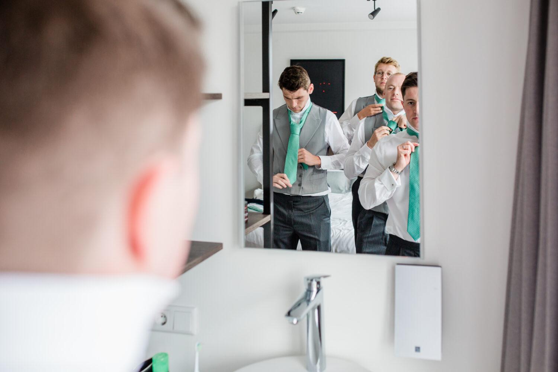 Een best man en groomsmen staan samen voor de spiegel hun stropdassen goed te doen.