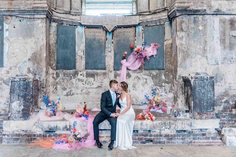 Een bruidspaar kust elkaar voor de backdrop van hun ceremonie bij Asylum Londen in Engeland